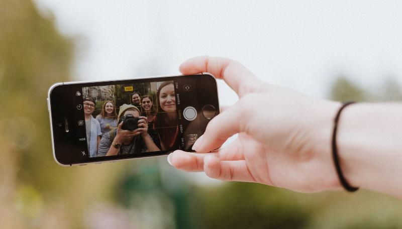 Eine Hand hält ein Smartphone, mit dem gerade ein Bild einer Gruppe junger Menschen gemacht wird.