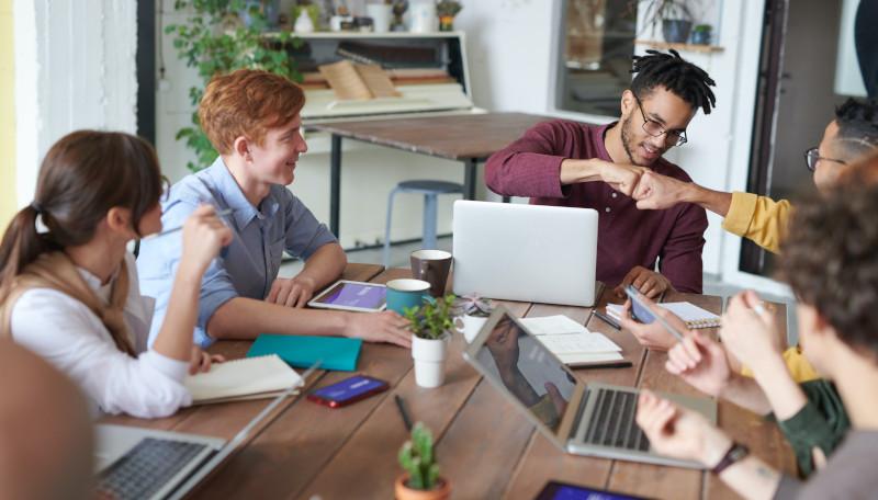 Fünf junge Menschen sitzen gemeinsam an einem Tisch und arbeiten zusammen an Tablets und Laptops.