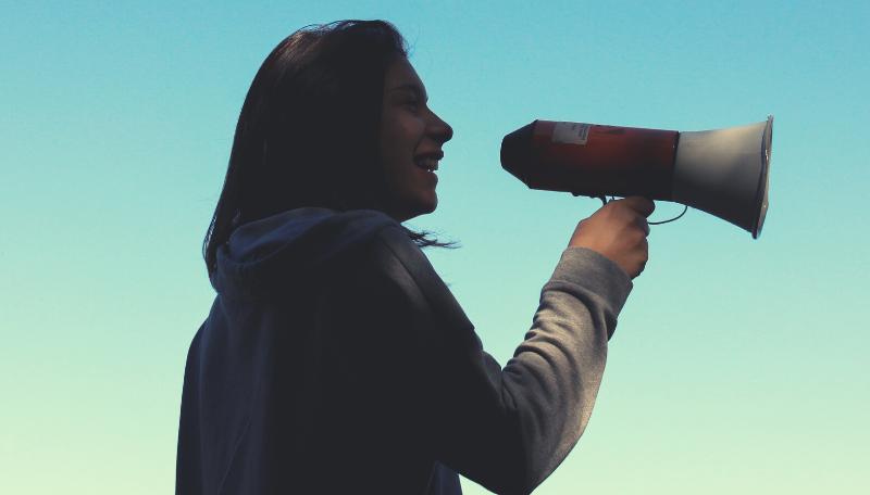 Person mit einem Megaphon in der Hand.