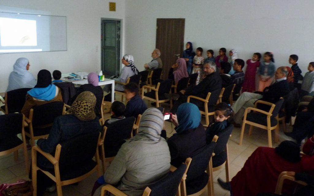 Foto der Filmvorführung bei der Abschlussfeier. Vielen Menschen sitzen in einem Raum und betrachten die Filmleinwand.