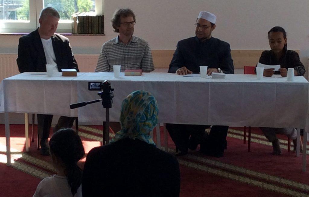 Foto von Theolog*innen, die an einem Tisch sitzen und interviewt werden.