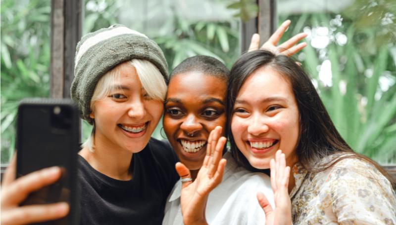 Drei Jugendliche stehen nebeneinander und kommunizieren gemeinsam per Videocall über ein Smartphone. Sie lachen und winken.