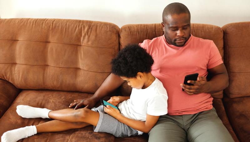 Ein Kind und eine erwachsene Person sitzen auf einem Sofa und schauen auf ihre Smartphones