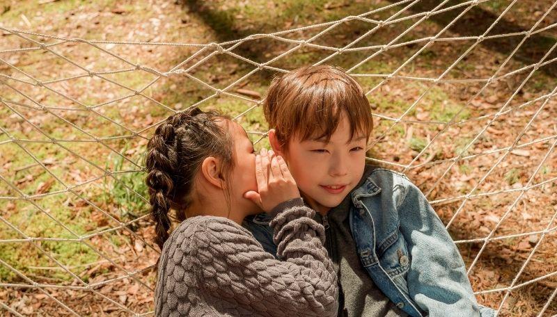 Ein Kind flüstert einem anderen Kind etwas ins Ohr.